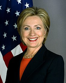 Formal pose of middle-aged white woman with shortish blonde hair wearing dark blue jacket over orange top with American flag in background