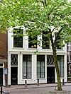 foto van Het Compas, een pand met in oorsprong bedrijfsruimte, twee woonlagen en een kapverdieping onder samenstel van pannen zadeldaken tussen puntgevels
