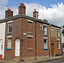 A two-story brick terraced house with chimney pots on its roof, attached to its neighbour, under a blue sky with clouds. Two of the windows on the front have been bricked in, and a small portion of the facade at upper right is concrete. A small black and white plate on the front identifies it as being on Barton Street. Around the corner is a white wooden door in a brick arch; at right is a similar doorway with a brown door.