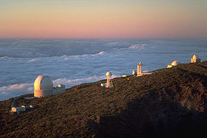 Series of white structures along the side of a mountain with a sea of clouds below and behind the mountain extending to the horizon which is red, orange, and yellow.
