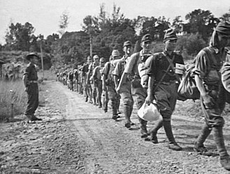 North Borneo - Disarmed Japanese troops marching towards a prisoner of war (POW) compound in Jesselton after surrendering to the Australian Imperial Force (AIF) on 8 October 1945.