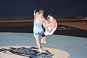 The college wrestler in light blue is attempting a takedown to the mat, but not without a counter by the defensive wrestler in white.