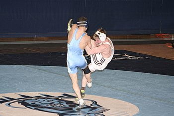 The college wrestler in light blue is attempting a takedown to the mat, but not without a counter by the defensive wrestler in white. Kicking Out.jpg