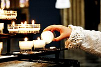 Votive candle being lit at a cathedral in Brussels
