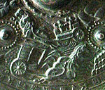Detail of a metal object showing embossed scene of a horse drawn chariot.