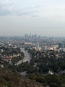 Photographie du centre-ville de Los Angeles vu depuis des collines éloignées, sous un ciel nuageux.