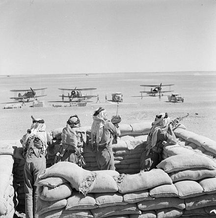 Gloster Gladiators of No. 94 Squadron RAF Detachment, guarded by Arab Legionnaires, refuel during their journey from Ismailia, Egypt, to reinforce Habbaniya Legionnaires guards gladiators.jpg