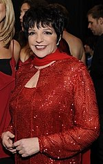 A woman in a red dress, jacket and scarf smiles toward the camera.