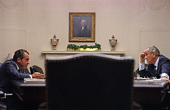 Nixon sits across a large table with President Johnson in the White House