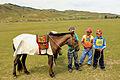 Młodzi jeźdźcy i konie na stepie podczas lokalnego festiwalu Naadam.jpg