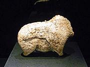 Photographie en couleurs sur fond noir d'une statuette en ivoire posée sur un socle anthracite et représentant le corps d'un bison.
