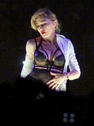 "Human Nature (Madonna song) - Madonna stripping off her clothes during the performance of ""Human Nature"" on The MDNA Tour (2012)."