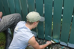 House painter and decorator - A man painting a fence green