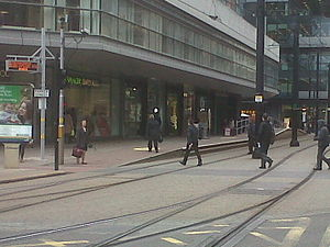 Mosley Street tram stop - The former station site. The passenger information display at the end of the platform tells passengers whether to go to Market Street or Piccadilly Gardens for trams to Altrincham.