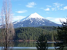 A conical, snow-capped mountain rises above a forest and a lake.