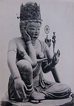 Three-quarter view of a seated statue with six arms. The left leg is bend, touching the ground along its whole length. The right leg is also bend, but with the knee up. The right foot is above the left foot. One of the right hands is touching the right ear, another is lifting a jewel-shaped object in front of the breast. One of the left hands carries a flower, another a small wheel-shaped object.
