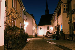 Kirchgasse in Niederwalluf, rechts der ehemalige Stadioner Hof, im Hintergrund die katholische Pfarrkirche St. Johannes der Täufer