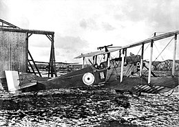 Side view of military biplane with pilot in cockpit, parked on landing ground