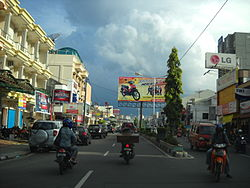 City street with cars, motorbikes and a billboard