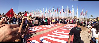 "United Nations Framework Convention on Climate Change - A ""family photo"" organized by Greenpeace, at the entrance to the United Nations, with a banner reading ""We Will Move Ahead"""