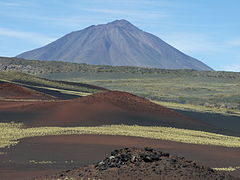 A volcanic cinder cone, with a conical mountain rising in the background