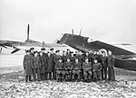 Personnel of 'B' Flight, No. 409 Squadron RCAF, pose for a formal portrait with one of their Beaufighter Mk IIs at Acklington, January 1942. CH4903.jpg
