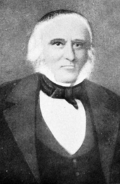 Formal portrait showing the head and shoulders of a white-haired man wearing a dark cape or coat