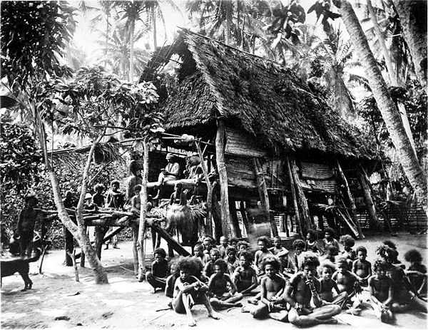 Black and white photograph of large building of logs with thatched roof.  A large group of people sit in the foreground.