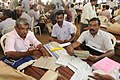 Polling officials checking Electronic Voting Machine (EVM) and other necessary belongings for use in the General Elections-2014, at the distribution centre, at Thycaud, Thiruvananthapuram, Kerala on April 09, 2014.jpg