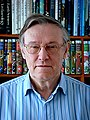 Portrait of John Birks in front of a bookcase.jpg
