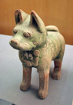 Economic history of China before 1912 - A pottery dog found in a Han tomb wearing a decorative dog collar; production of ceramic figurines represented a significant part of the funerary industry, which produced goods such as this for a tomb occupant's afterlife.