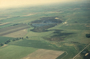 Pothole (landform) - An aerial photo of a prairie pothole with a road through the center