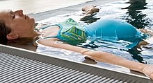 A pregnant woman floats in the corner of a swimming pool