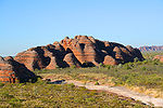 Large red sandstone rock formation surrounded by shrubbery and open plains