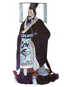 Dessin d'un homme debout, portant de lourds vêtements amples et une coiffe à longues franges devant et derrière la tête.