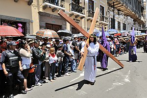 Holy Week - A Good Friday procession in Ecuador. The man is shown holding a cross, which Jesus was crucified on.