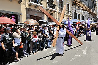 Holy Week - A Good Friday procession in Ecuador. The man is shown holding a cross, representing the one upon which Jesus was crucified.