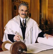 A gray-haired man with a full mustache faces the viewer, wearing a large skullcap, round wire-rimmed glasses, black suit with white shirt and patterned tie, and a full white prayer shawl with light gray stripes. On a table before him is an open Torah scroll; his left hand rests on one side of the scroll, and his right hand holds a silver pointer pointed at the words written on the scroll. A wall and part of a closed Torah ark are visible behind him.