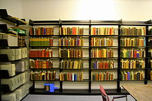 Several wall-mounted bookshelves contain books of various colors
