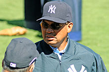 "An African American male in his sixties wearing a cap and jacket, both with a logo of an overlapping ""N"" and two overlapping ""Y""s, and sunglasses, stands on a baseball field."