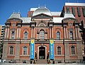 "Photograph of the Renwick Gallery, an old brick building with colorful contemporary banners flanking the main entry and announcing ""American Craft""."