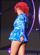 A woman with red hair, wearing an electro blue skirt.