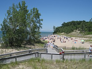 Photograph showing a sandy beach with sunbathers and Lake Ontario in the distance.