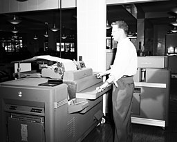 Seattle City Light worker with office machine, 1954