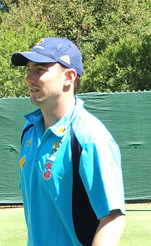 A head and shoulders photograph of a sportsman taken outside and from his right side whilst wearing a blue shirt and baseball hat looking to the right of the photograph