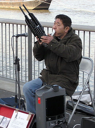 Sheng (instrument) - Sheng player Guo Yi beside the River Thames, London, England