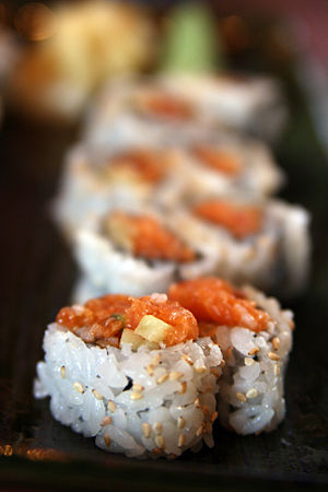 Spicy salmon sushi with sesame seeds.