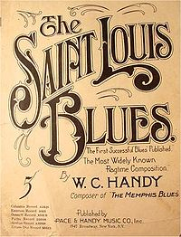 "Vaaleanruskea sivu, jolle on isoilla tummanruskeilla kirjaimilla kirjoitettu ""The Saint Louis Blues."" Tekstin alla lukee pienemmällä ""The First Successful Blues Published. The Most Widely Known Ragtime Composition. By W. C. HANDY, Composer of 'The Memphis Blues'"". Alalaitaan on kirjoitettu ""Published by Pace & Handy Music Co. Inc., 1547 Broadway, New York, N.Y."" Vasemmassa laidassa on isolla numero 5 ja alla pienellä tekstillä listattu levynnumeroita."