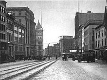 A black and white photograph showing the post office tower in the middle of other buildings on one side of a street with tracks down the middle