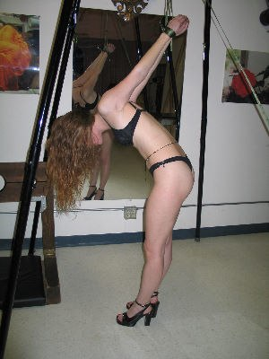 Strappado bondage - A woman forced to experience increased shoulder strain from being pulled upward.